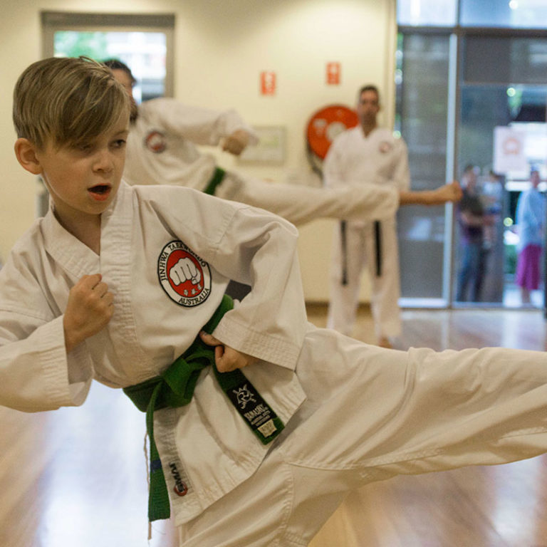 child doing a sidekick with a green belt